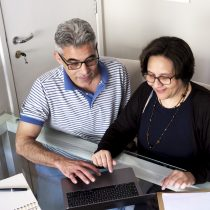 A senior, heterosexual Brazilian couple in their fifties sitting at a dining room table in a domestic, modern apartment setting and sharing a laptop computer